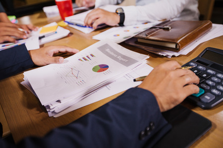 Geschäftsleute verwenden Taschenrechner und analysieren Geschäftsdaten und zeichnen Finanzdiagramme, die bei der Sitzung arbeiten.