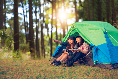 A group of Asian friends tourist drinking together with happiness in Summer while having camping Stock Photo