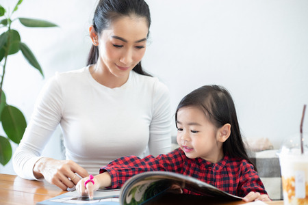 Mom is teaching her daughter to read a book.