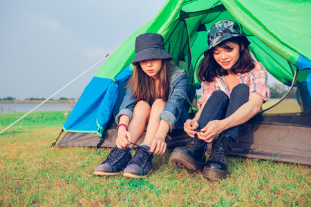 A group of Asian friends tourist Tie a shoe near tent with happiness in Summer while having camping