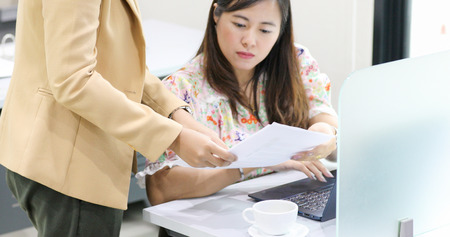 Asian businesswoman serious about the work and using notebook for business partners discussing documents and ideas at meeting Stock Photo