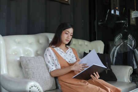 Asian women reading book and smiling and happy Relaxing in a coffee shop