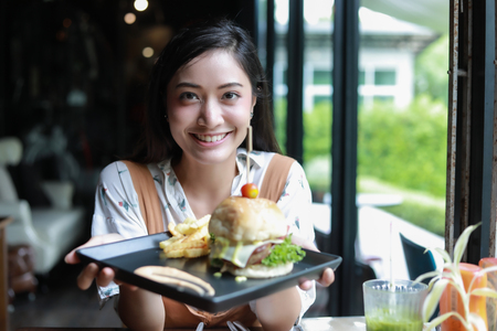 Asian women smiling and happy and enjoyed eating hamburgers at coffee and restaurant on relax time Stock Photo