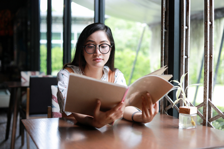 Asian woman open menu for ordering in coffee cafe and restaurant and smiling for happy time Banque d'images - 124895436