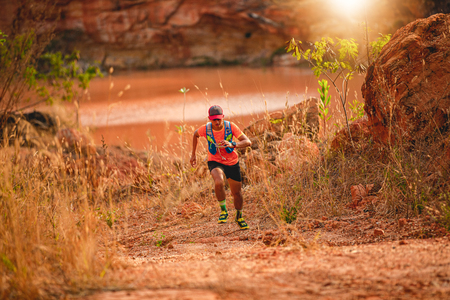 A man Runner of Trail . and athletes feet wearing sports shoes for trail running in the mountains