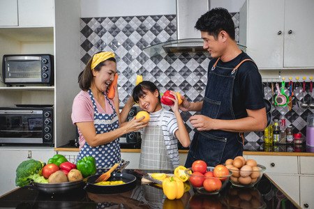 Happy Family have Dad, Mom and their little daughter Cooking Together in the Kitchen