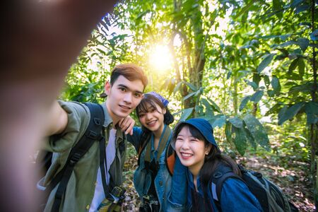 Asian Group of young people with friends and backpacks walking together and happy friends are taking photo and selfie ,Relax time on holiday concept travel Reklamní fotografie - 124897389