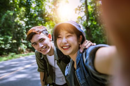 Asian Group of young people with friends and backpacks walking together and happy friends are taking photo and selfie ,Relax time on holiday concept travel