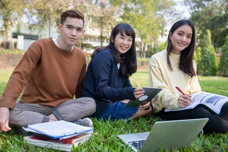 Group Of University Students asian sitting on the green grass  Working and reading Outside Together in a park