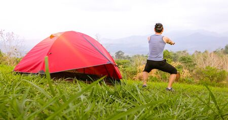 A man exercise and Athlete Warming Up in morning near tent on camping trip on the mountain Stock Photo