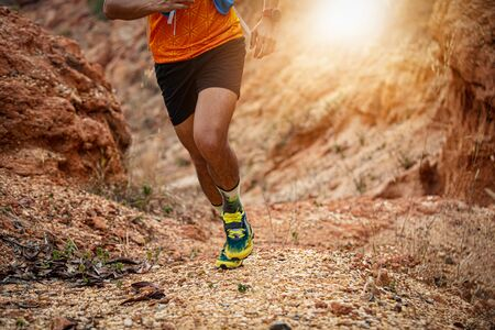 A man Runner of Trail. and athlete's feet wearing sports shoes for trail running in the forest