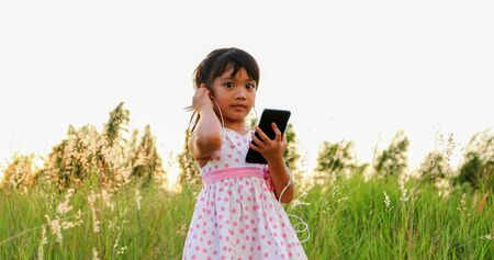 Asian child girl Listening to music and singing from a mobile phone and happy on meadow in summer in nature