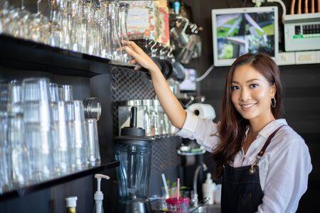 Aziatische vrouwen Barista die en koffiemachine in de teller van de koffiewinkel glimlachen gebruiken - het Werk van de de eigenaarvoedsel en drank van de vrouwen kleine onderneming koffieconcept