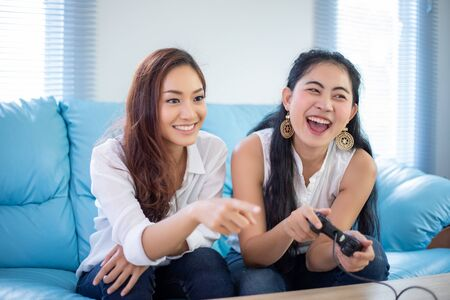 two women Competitive friends playing video games and excited happy cheerful at home 写真素材 - 128801835
