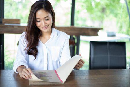 Azjatycka kobieta otwiera menu do zamawiania w kawiarni i restauracji i uśmiecha się na szczęśliwy czas