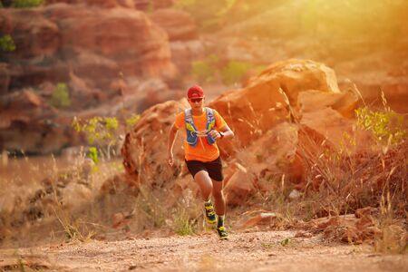 Ein Mann Runner of Trail und Sportlerfüße mit Sportschuhen für Trailrunning im Wald