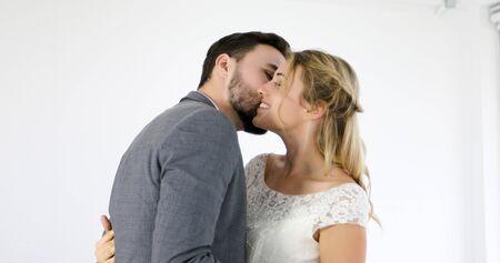 Gli amanti regalano fiori alla sposa e si baciano felici e la coppia ama in piedi nello studio del matrimonio