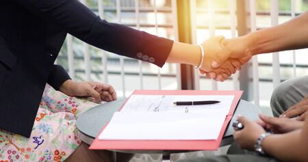Business people shaking hands and smiling their agreement to sign contract and finishing up a meeting