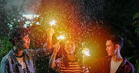 Asian group of friends having outdoor garden barbecue laughing with alcoholic beer drinks and showing group of friends having fun with sparklers on night