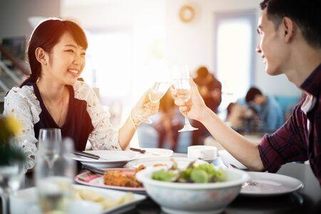 Asiatisches junges Paar, das ein romantisches Abendessen am Abend genießt, während es zusammen am Esstisch in der Küche sitzt