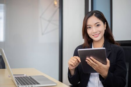 Asian business women using tablet  for working at office relax time and smiling Stok Fotoğraf