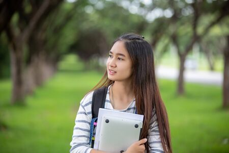 beautiful Asian girl student holding books and smiling at camera and learning and education concept  on park in summer for relax time