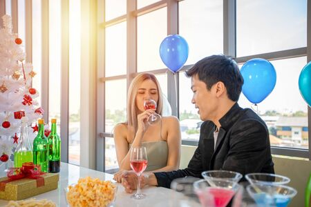Asian Couple lover having party with alcoholic beer drinks and Young people enjoying at a bar toasting cocktails with Christmas gift in Christmas holiday and happy new year patty