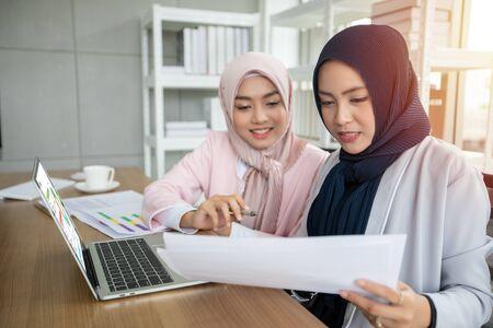 Muslimische Geschäftsfrau in traditioneller Kleidung, die beim Treffen im Büro arbeitet und diskutiert