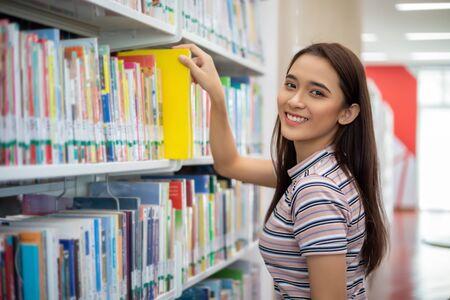 Étudiantes asiatiques souriant et lisant un livre dans une bibliothèque