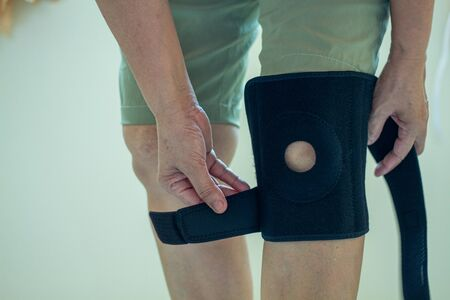 old Asian women to knee injury and use knee support brace on leg Stock Photo