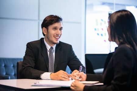 Businessmen and Businesswomen discussing documents for job interview concept