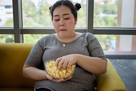 Overweight woman and asian girl enjoy eating food and popcorn on sofa at home