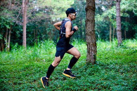 A man Runner of Trail and athlete's feet wearing sports shoes for trail running in the forest Banco de Imagens
