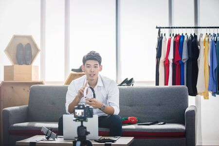 Asian man blogger broadcasting a video for selling product online such as Hats, shoes, headphones, clothing, safety headers.Shopping online concept at home