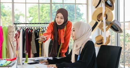 Small business of Muslim woman fashion designer Working and using smart phone and tablet With Dresses at clothing store