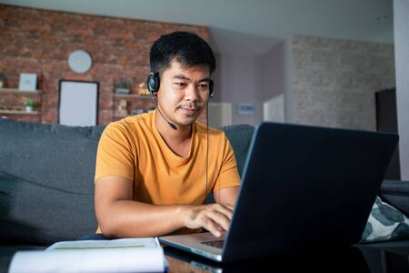 Asian businessmen is using notebook computers and wear headphones for online meetings and working from home. Imagens