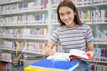 Asian female students smiling and reading Book in library