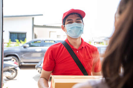Asian delivery servicemen wearing a red uniform with a red cap and face mask handling cardboard boxes to give to the female customer in front of the house. Online shopping and Express delivery