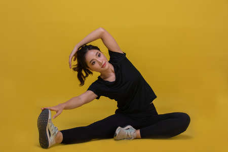 Smile happy Beautiful portrait young Asian woman stretching exercise workout on yellow background, fitness sport girl aerobic and healthy concept. Reklamní fotografie
