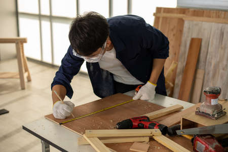 Asian man Carpenter working with technical drawing or blueprint construction paper lying on a workshop with carpentry tools and wood at home