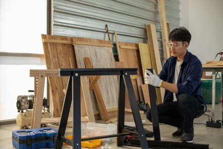 Asian man Carpenter working with technical drawing or blueprint construction paper lying on a workshop with carpentry tools and wood at home Reklamní fotografie