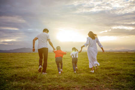 Asian family walking and running on the Meadow at sunset with happy emotion. Family, Holiday and Travel concept. 版權商用圖片