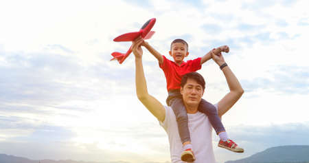 Father and son playing toy airplane on the Meadow at sunset with happy emotion. Family, Holiday and Travel concept.