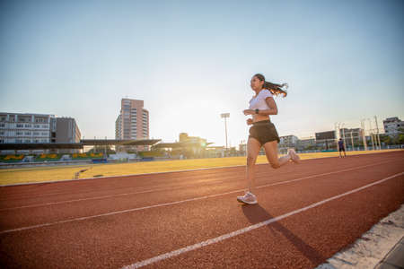 Asian Young fitness woman runner running on stadium track