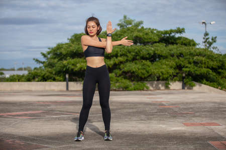 smiling women asian runner doing stretching exercise, preparing for morning workout and lifestyle concept on city