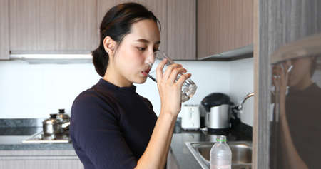 Asian woman drinking water on glass in kitchen
