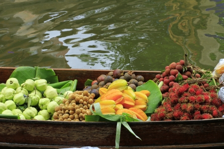 long-tail boat with fruits on the floating market  photo