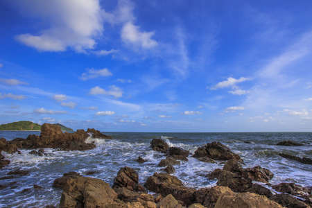 ocean waves crashing onto the rocky shore with beautiful sky , Thailand  photo