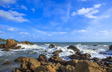 ocean waves crashing onto the rocky shore with beautiful sky , Thailand