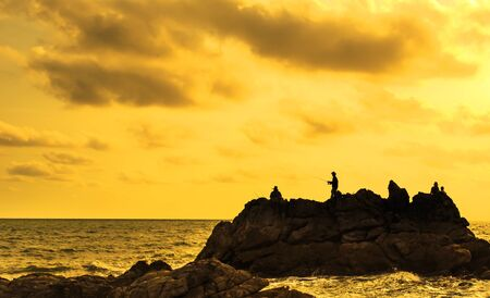 silhouette image of traveler at the sea and beautiful sunset